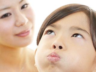 母親の前で口を尖らす女の子