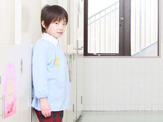 幼稚園の廊下に一人で立つ子供