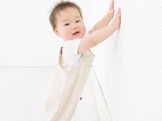 壁につかまり立ちする赤ちゃん