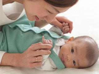 赤ちゃんの手を持ってあやす母親と顔をそむける赤ちゃん