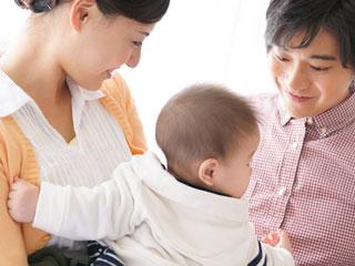 母親に抱っこされる赤ちゃんを父親が見守る