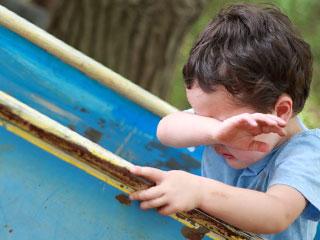 滑り台につかまりながら泣く子供