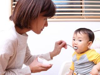 赤ちゃんの口にスプーンを運ぶ母親