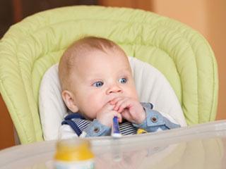 椅子に座ってスプーンを口に入れて待つ赤ちゃん