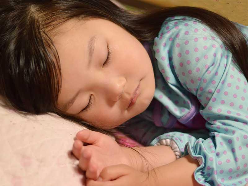 頭が痛くて寝ている女の子