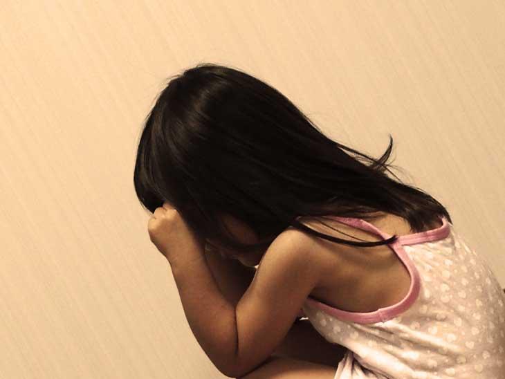 頭痛でこめかみを押さえている女の子