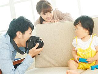 子供の写真を撮る父親と見守る母親
