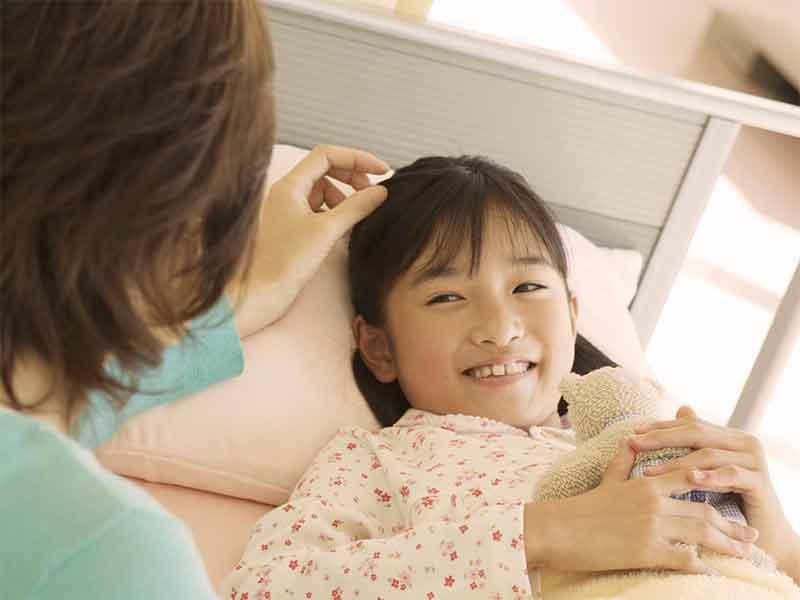 布団で横になっている女の子の頭をなでてあげる母親