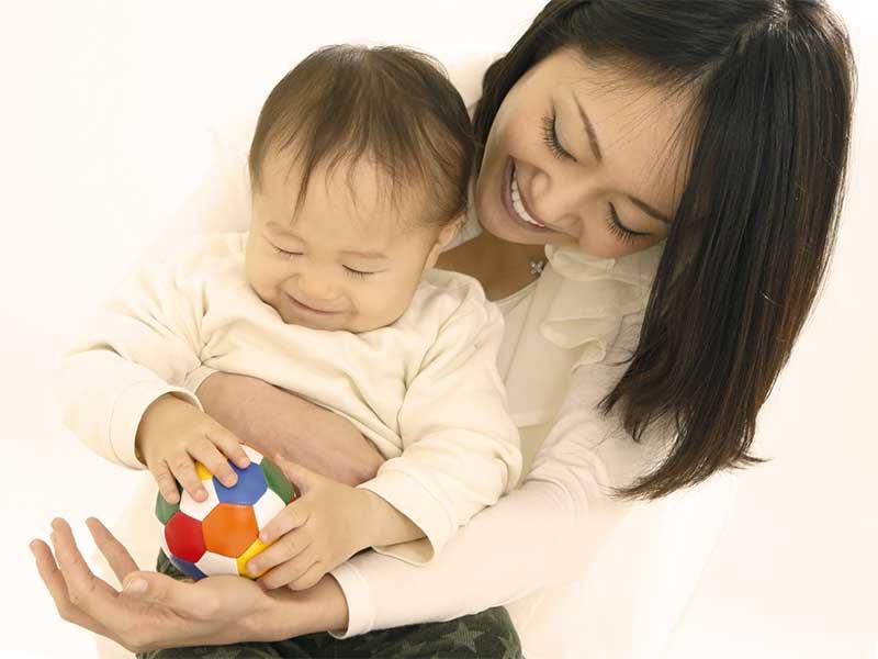 子供を膝枕して抱きかかえる母親