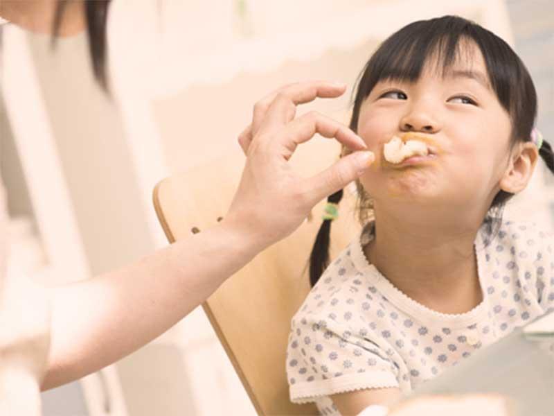 お惣菜をママの手で食べさせてもらっている女の子