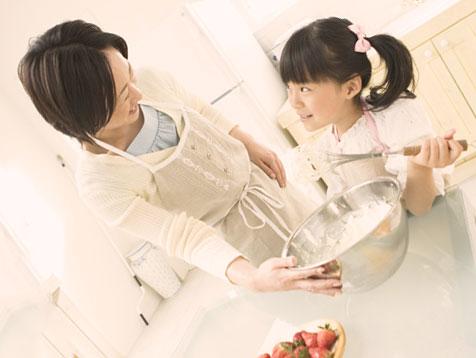 母親と一緒にケーキを作っている女の子