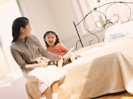ベッドの上で母親に絵本を読んでもらっている女の子