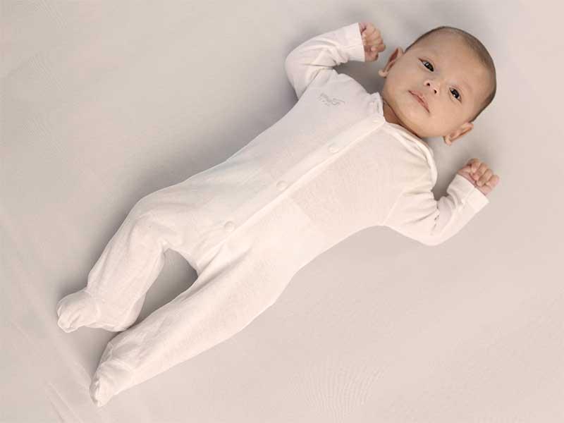 足を伸ばした状態で仰向けで寝ている新生児