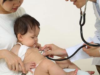 赤ちゃんの体に聴診器を当てる医師