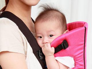 抱っこひもでお母さんと向かい合って抱かれる赤ちゃん