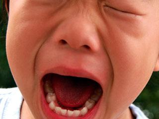口を大きく開けて叫ぶ子供