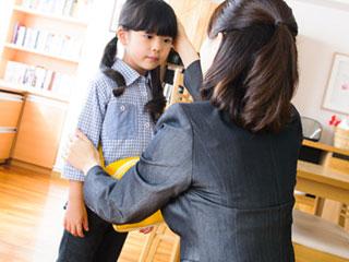 幼稚園のバッグを肩に掛けて母親に頭をなでられる子供