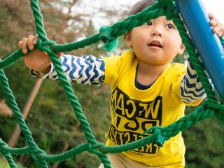 戸外の梯子ネットで遊ぶ子供