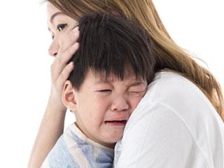泣く子供を抱きしめる母親