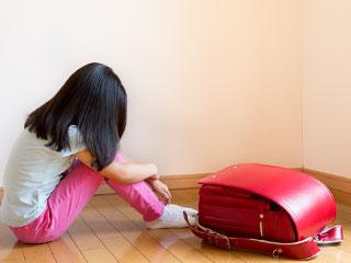 ランドセルを置いたまま床に座り込む小学生の女の子