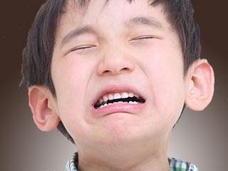 目を閉じたまま泣く子供