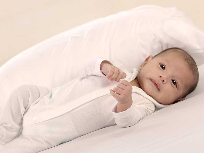 クッションのおかげで横向きに寝ている赤ちゃん
