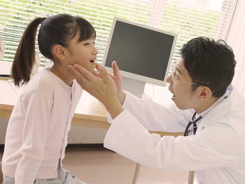 女の子の首にできたしこりの硬さを確認している男性医師