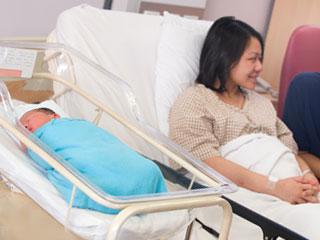 出産後の女性の傍らに赤ちゃんが眠る