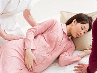 看護師に横向きにされる妊婦