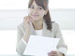 会社で書類を手に取って見る女性