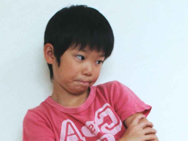 環軸椎回旋亜脱臼で首が曲がったまま困った顔をしている男の子