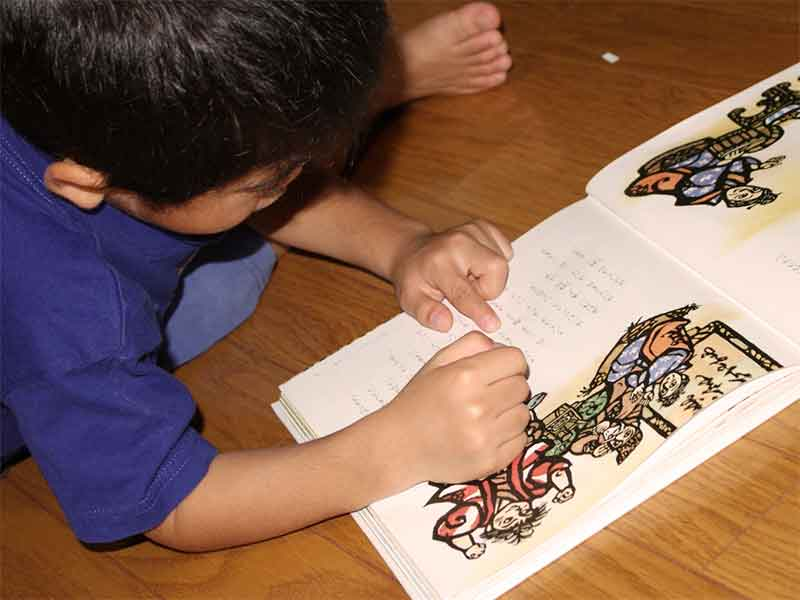 床で無理な体勢で絵本を読んでいる子供