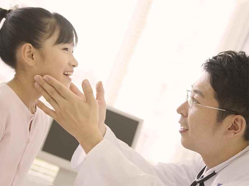 病院で医者に首を診察してもらっている女の子