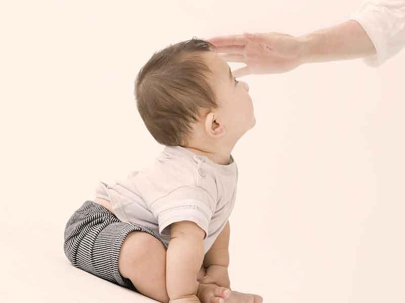 赤ちゃんの頭を撫でている母親の手