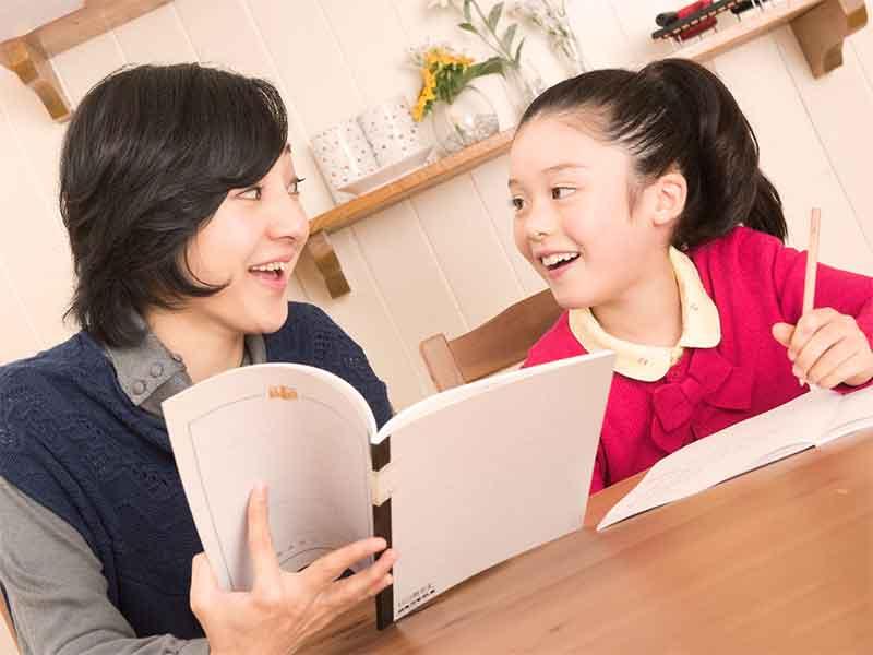母親に勉強を見てもらって笑顔の女の子