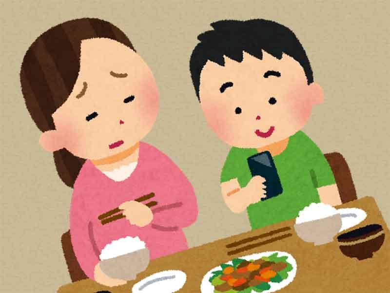 ご飯を食べながらスマホを触っている小学生の男の子