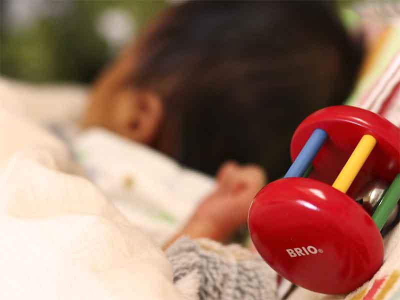 寝ている生後1ヶ月の赤ちゃんとガラガラのおもちゃ
