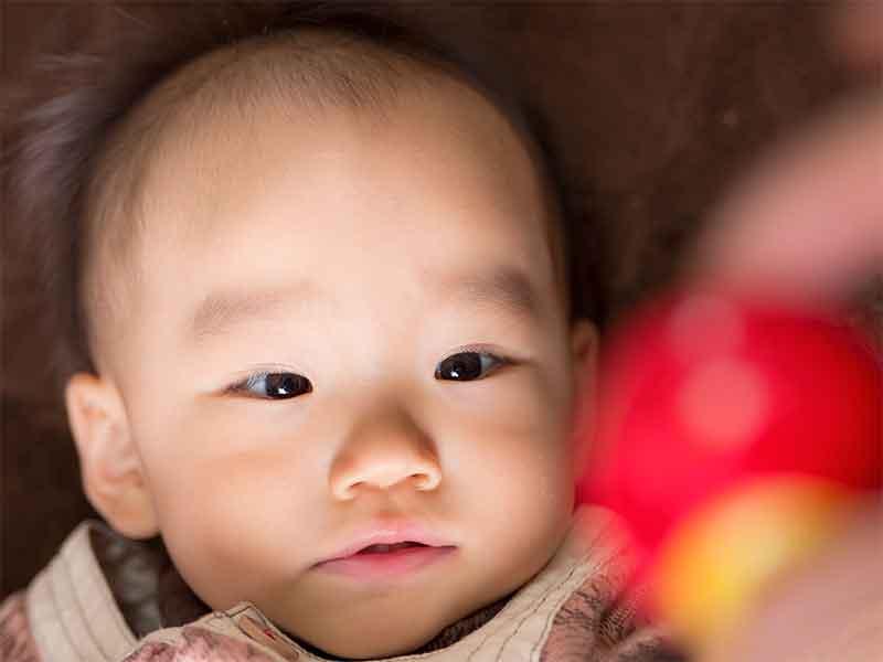 赤いおもちゃを見ている3ヶ月の赤ちゃん