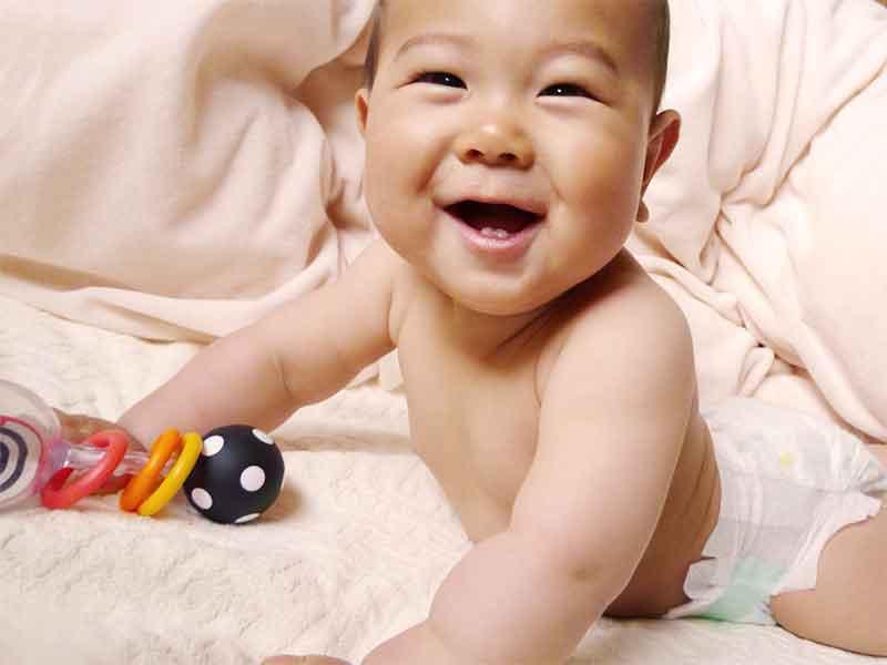 片手におもちゃを持って上半身を起こしている6ヶ月の赤ちゃん