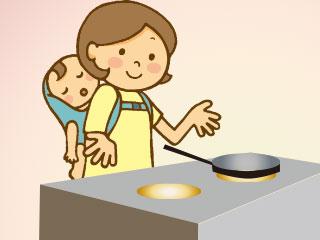 赤ちゃんをおんぶして料理する母親
