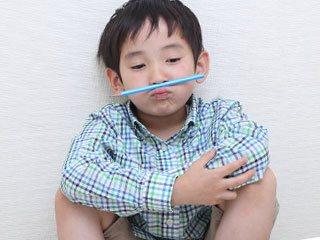 鼻の下に鉛筆をはさんでふてくされる子供