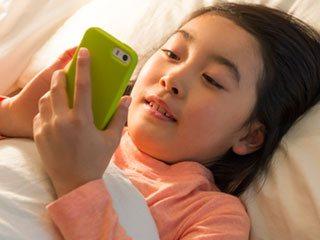 ベットで寝ながらスマホを操作する子供