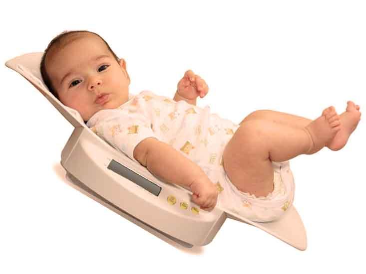 新生児用体重計で体重を量られている新生児