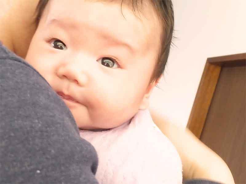 抱っこで背中をトントンされてもゲップがなかなか出ない新生児の顔