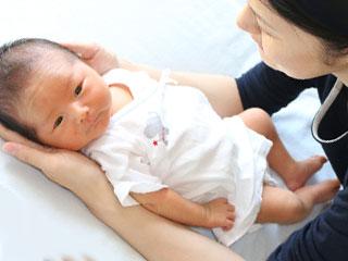 赤ちゃんを両手で暖めるお母さん