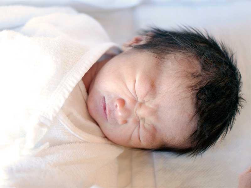 床に苦しそうな顔で寝ている新生児