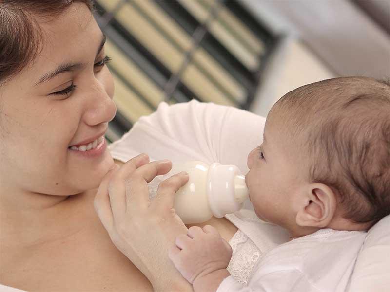 新生児にミルクを与えているママ