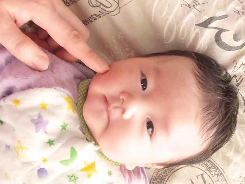 新生児の頬に人差し指でベビーオイルを塗る母親