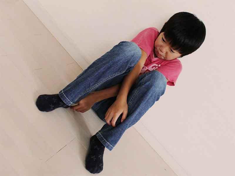 壁に寄りかかりながら座って泣いている男の子
