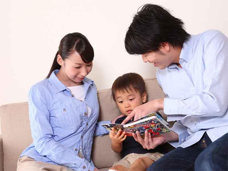 子供を挟んで絵本を一緒に読み聞かせしている夫婦